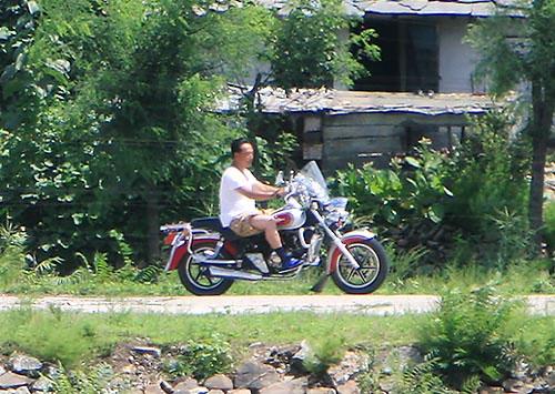 中国製バイクで鴨緑江沿いを疾走する北朝鮮の男性