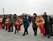 銅像に花輪を捧げる人々