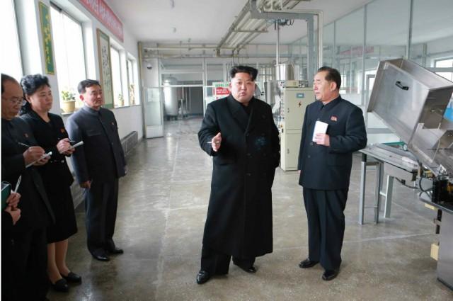 タバコを手に挟んで工場で現地指導する金正恩氏