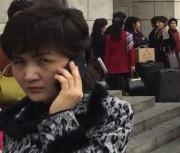 平壌駅前でスマホを使う女性