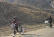 自転車に荷物を積んで市場に向かう北朝鮮の人々(資料写真)