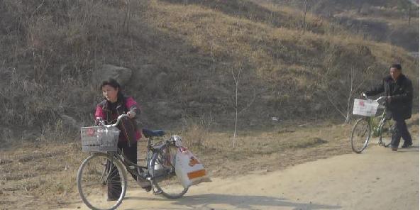 自転車に荷物を積んで市場に向かう人々