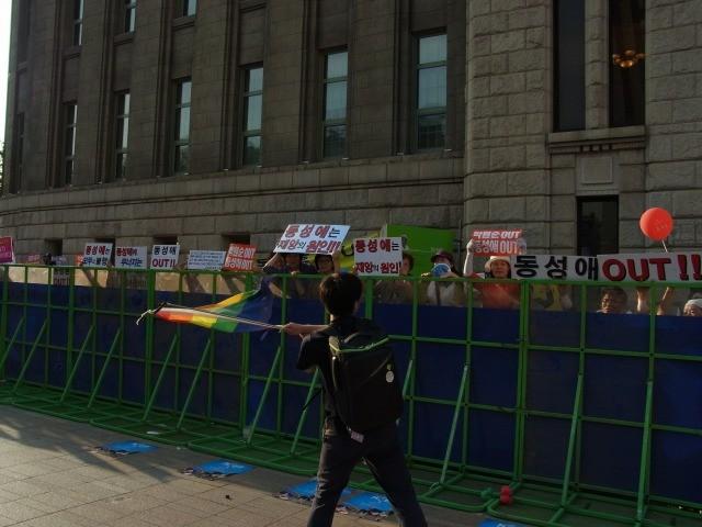 会場を囲む防護柵にびっちり張りついてイベントに抗議するプロテスタント系団体関係者に、レインボーフラッグで応戦。(画像:筆者提供)