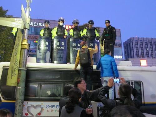 大型バスを並べた「防壁」の上で市民から抗議を受ける警察官たち