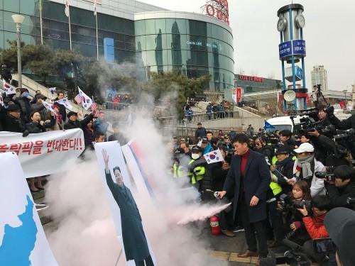 保守系市民団体の集会で北朝鮮国旗が燃やされそうになったのを、韓国警察が消火器で制止した(2018年1月22日、デイリーNKジャパン編集部)