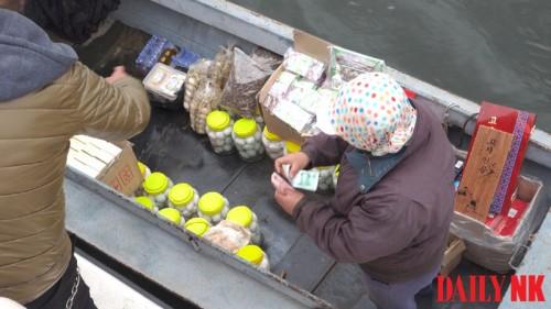 昨年4月、鴨緑江を運航する船で品物の取引をする様子(画像:デイリーNK)