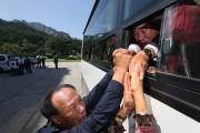 第2次面会の最終日となった26日、バスに乗り韓国への帰路につく息子(67)が北朝鮮に暮らす父(88)の手を握り別れを惜しんでいる(韓国ニュース通信取材団)