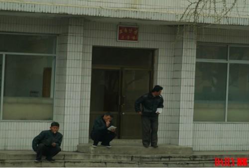 元山市内の交通安全教養室の前で交通安全教本を手に持ち喫煙する人々。交通違反を摘発され再教育を受けている。(画像:デイリーNK内部情報筋)
