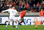 2010年サッカーW杯の最終予選で韓国の朴智星にタックルする金英俊(ニューシスKorea)